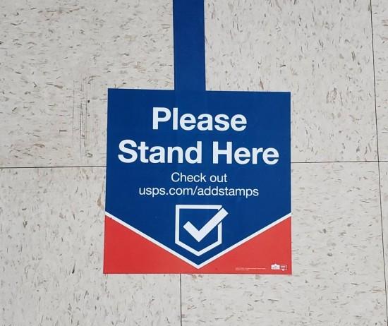 USPS social distancing floor decal.